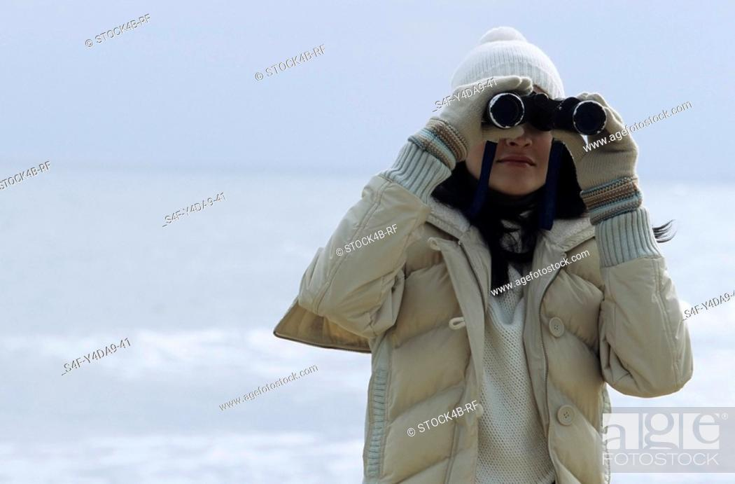 Stock Photo: Young brownhaired Woman with woolen Hat looking through Binoculars - View - Leisure Time - Coldness - Beach.