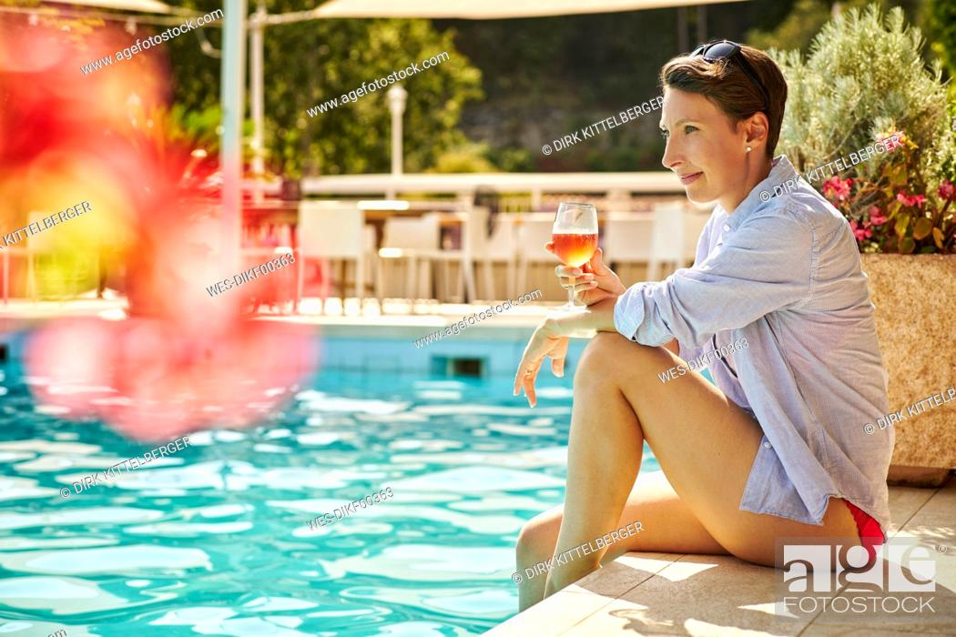 Stock Photo: Mature woman sitting at poolside with glass of blush wine.