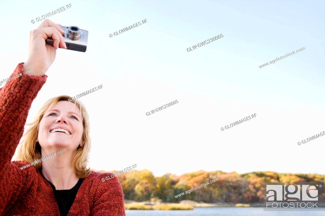 Stock Photo: Mature woman photographing with a digital camera and smiling.
