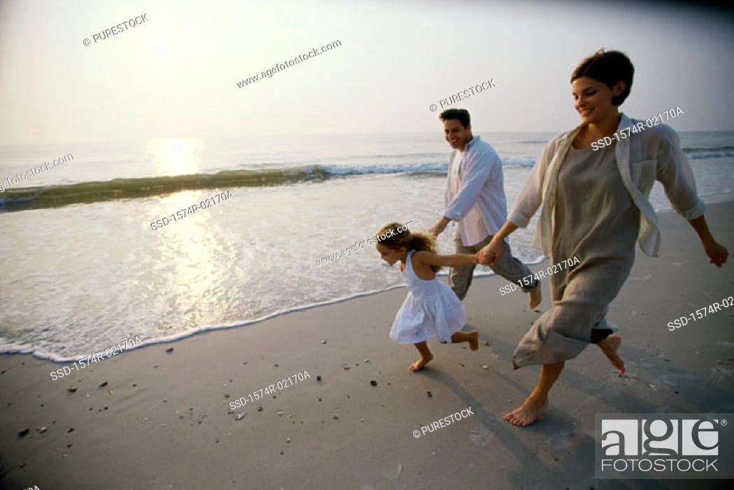 Stock Photo: Parents running with their daughter on the beach.