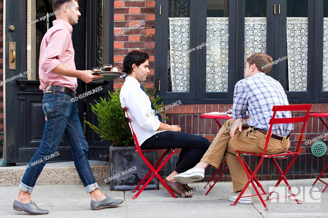 Stock Photo: Waiter bringing coffee to men outside cafe.