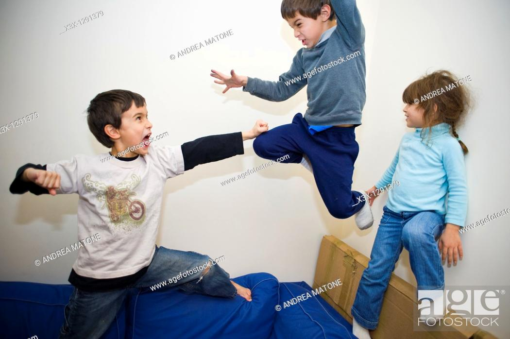 Stock Photo: Male children play fighting on the sofa.