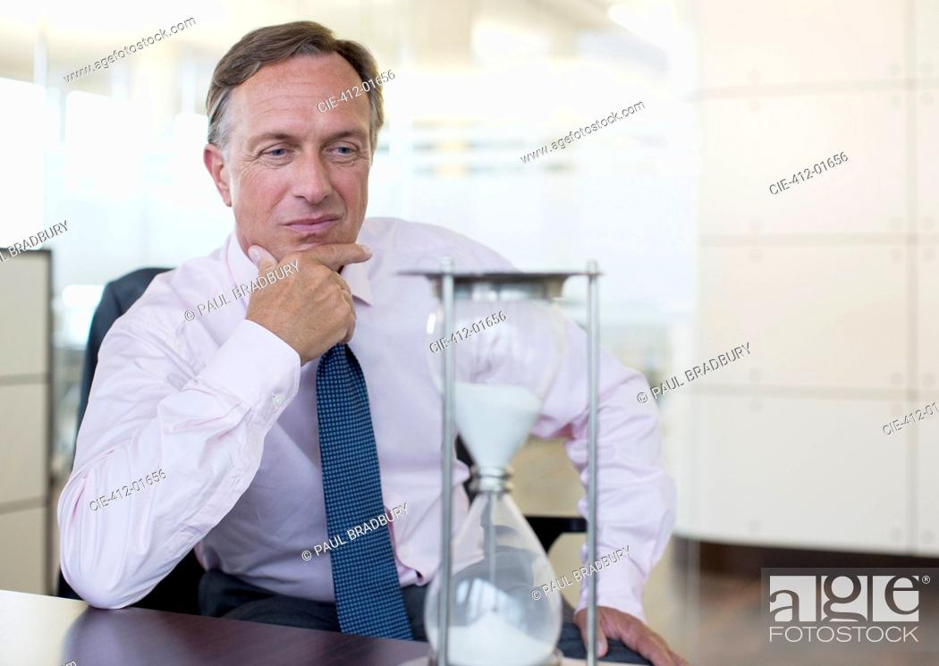 Stock Photo: Businessman watching hourglass in office.