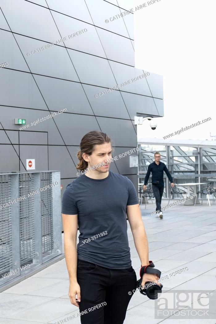 Stock Photo: Two young men dressed in black jeans alternately saunter and stride across the roof top terreace of the Confluence Museum; Lyon; France.