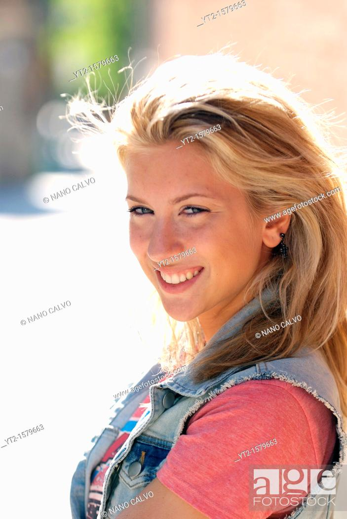 Stock Photo: Cute young blonde woman in urban setting.