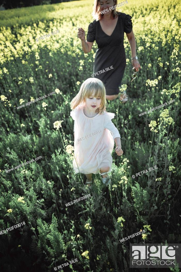 Stock Photo: Portrait of little girl walking on rape field with her mother.