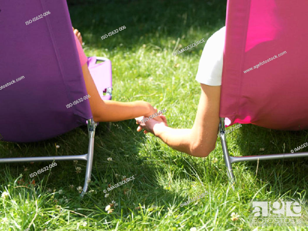 Stock Photo: Young couple relaxing on lounge chairs.