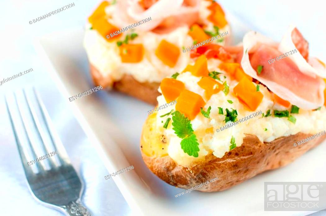 Stock Photo: White cheese cream and prosciutto in the potato.Selective focus on the front potato.