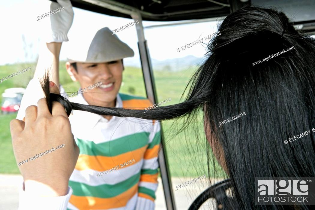 Stock Photo: View of a couple chatting at a golf cart.