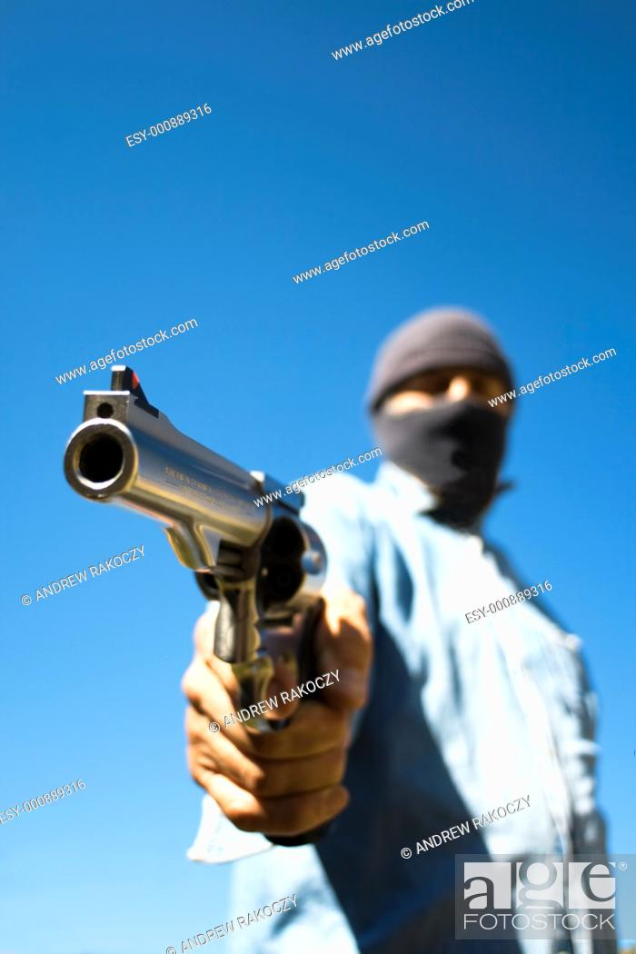Stock Photo: Hooded man with 44 magnum revolver threatening, wide angle view.