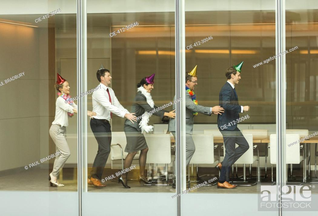 Imagen: Business people wearing party hats dancing in conga line at conference room window.