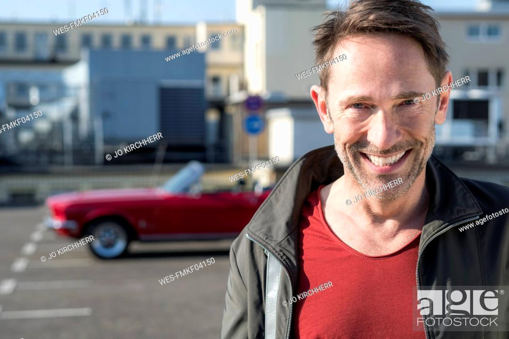 Stock Photo: Portrait of smiling mature man in front of his sports car on parking level.