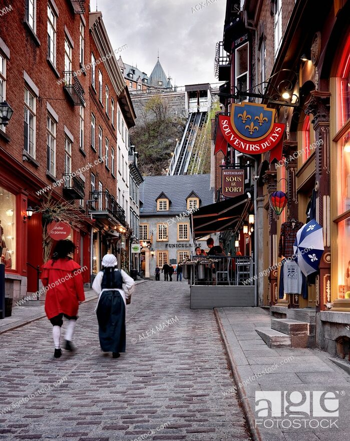 Stock Photo: Two people in medieval costumes walking up the Rue Sous Le Fort street in old Quebec City with funicular in the background.