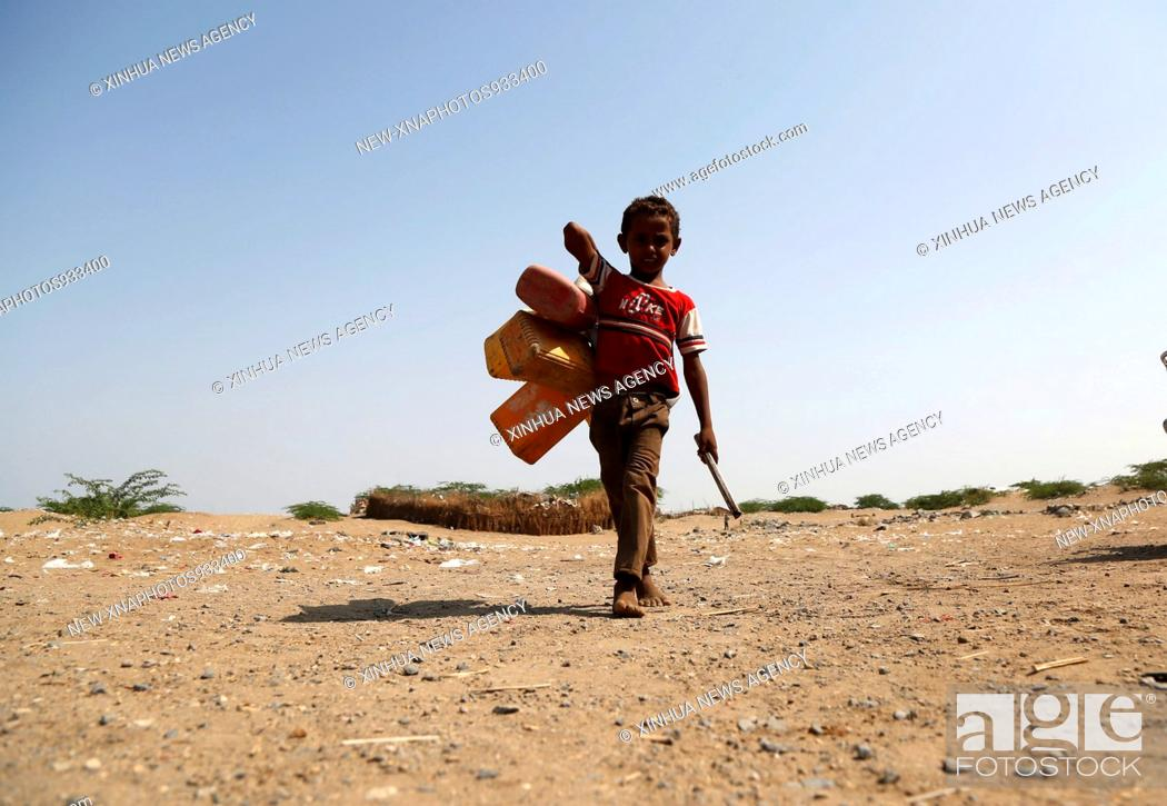 Stock Photo: (181001) -- HODEIDAH, Oct. 1, 2018 (Xinhua) -- A boy walks on the way to collect water from a charity pump near the port of Hodeidah, Yemen, on Sept.