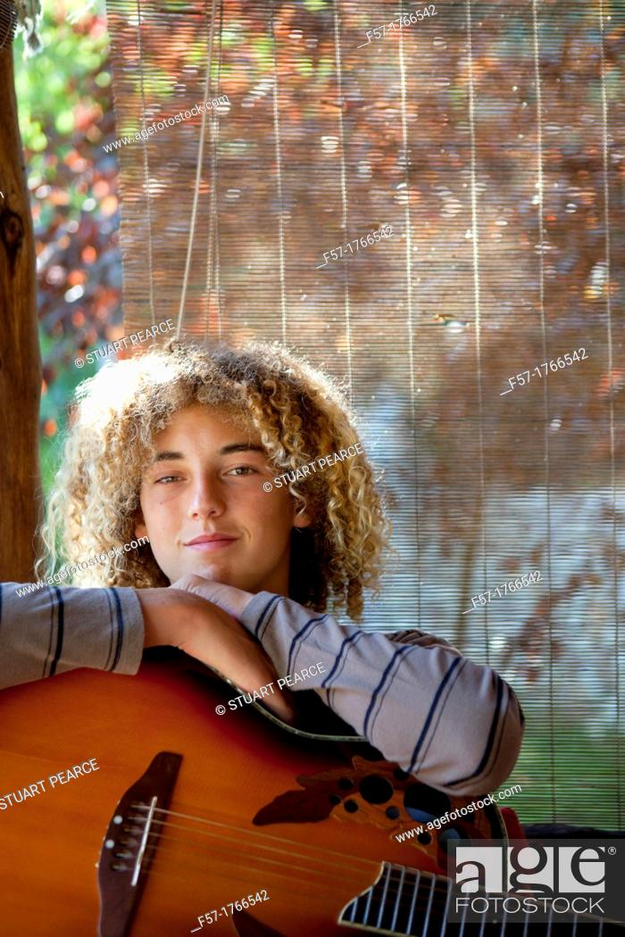 Stock Photo: Teenage musician with his guitar.
