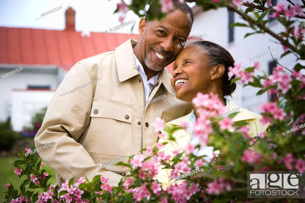 Stock Photo: Close-up of a senior man and a senior woman smiling behind flowers.