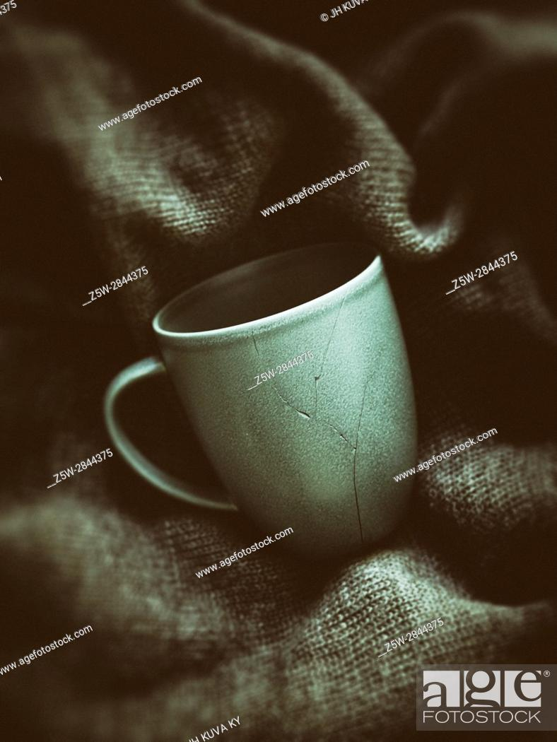 Stock Photo: Broken coffee cup pieces has been glued together, green pullover on background.