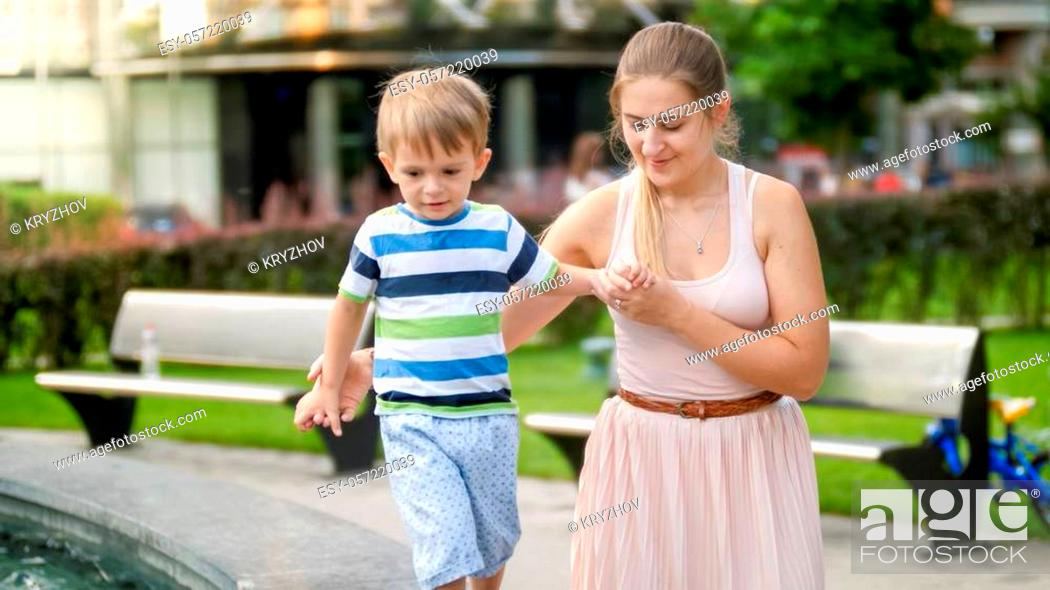 Stock Photo: Portrait of mother holding and supporting her 3 years old toddler boy while walking in park.
