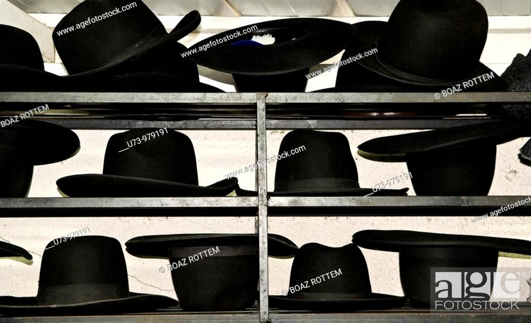 Stock Photo: Hats in order.Orthodox Jewish men that pray and learn the bible keep their traditional hats on the shelf.