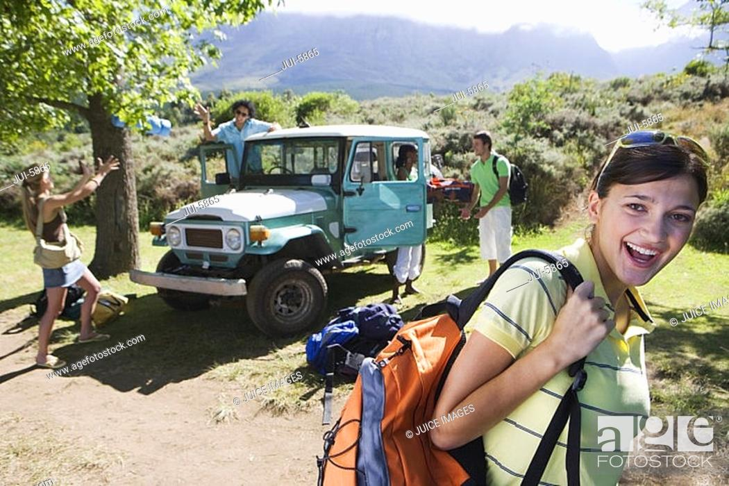 Stock Photo: Group of young adults departing on hiking trip, man unloading jeep, focus on woman in foreground, smiling.