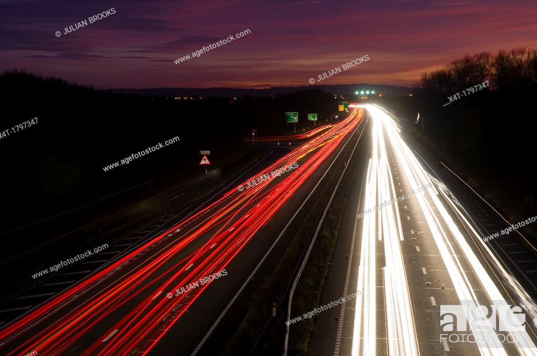 Stock Photo: busy main road with sunset sky and traffic light trails.