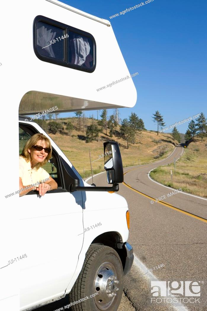 Stock Photo: Woman leaning out of window of motor home, smiling, portrait.