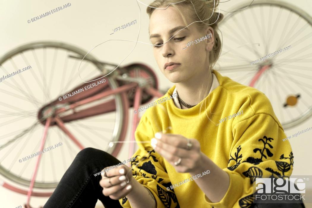 Stock Photo: young creative woman thinking about inspiring solutions in workshop, in Germany.