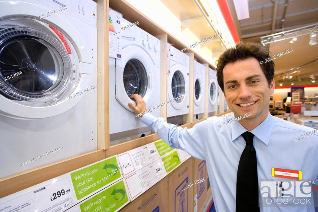 Stock Photo: Young salesman by washing machines, smiling, portrait.