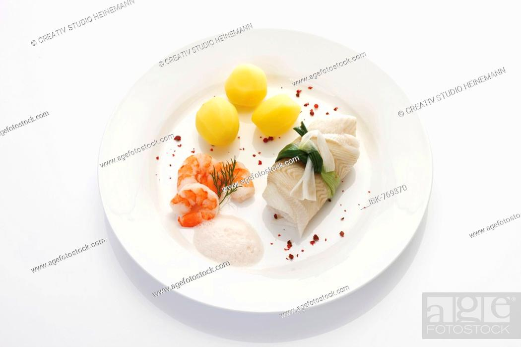 Stock Photo: Seafood dish: rolled halibut wrapped in a leek bow with boiled potatoes, shrimp (prawns) and frothy white wine sauce.