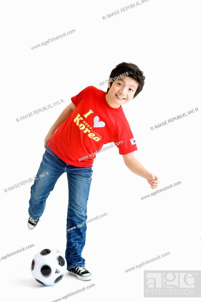 Stock Photo: boy kicking soccer ball.