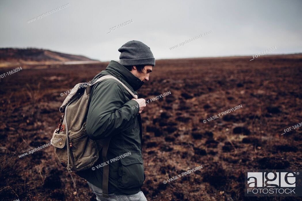 Stock Photo: Side view of hiker carrying backpack while walking on barren landscape, Blagoveschensk, Amur, Russia.