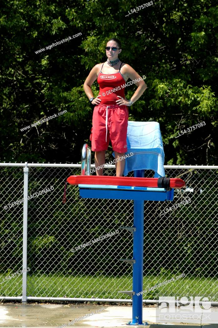 Stock Photo: Life guard on duty at a public swimming pool.
