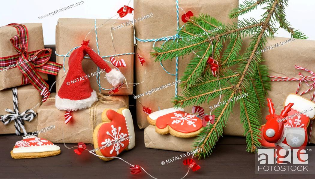 Stock Photo: gift box and baked Christmas gingerbread cookies, burning holiday lights on a brown table.