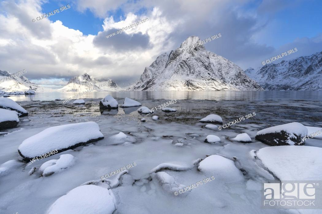 Imagen: Olstinden peak in winter, with ice and snow on the rocky beach in the foreground. Reine, Nordland county, Northern Norway region, Norway.