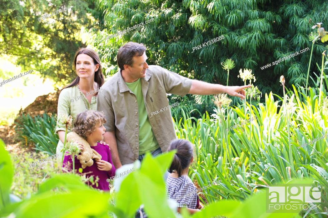 Stock Photo: Two little children walking in a garden with their parents.