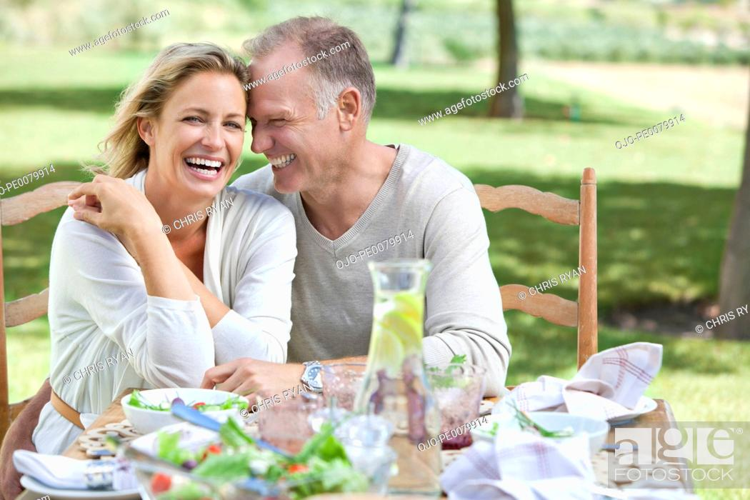 Stock Photo: Happy couple eating lunch at patio table.