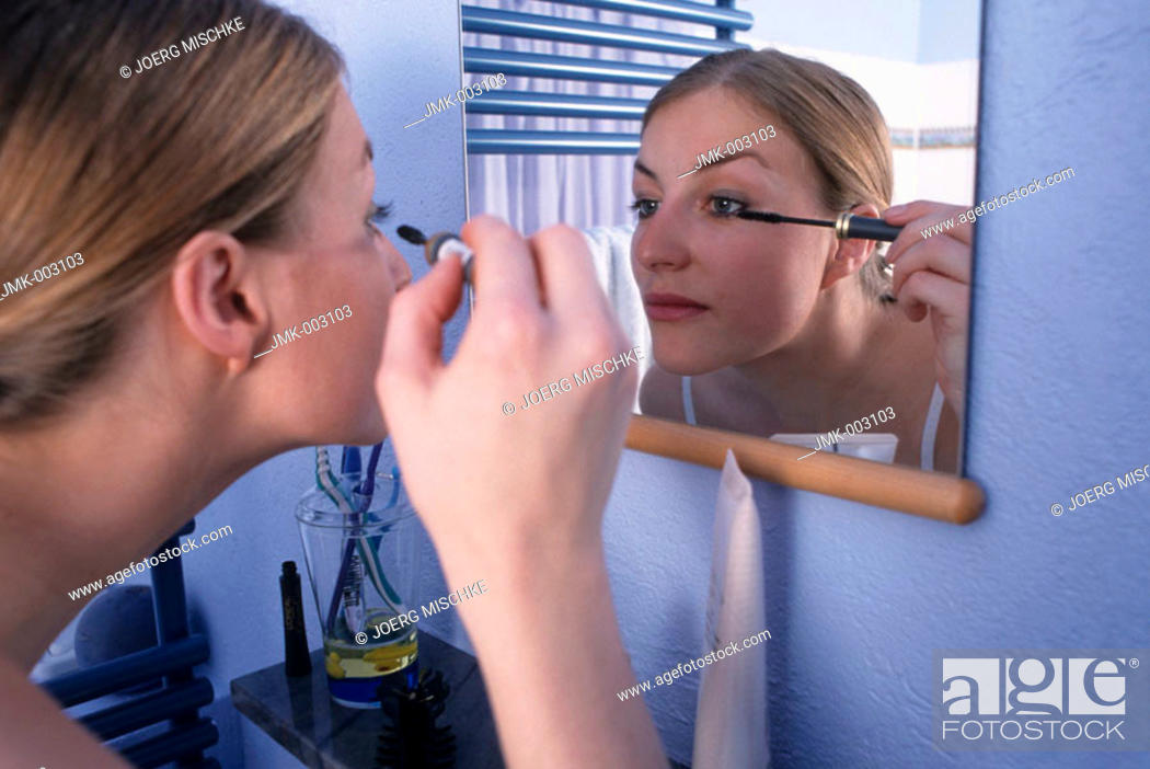 Stock Photo: A young woman, 20-25 25-30 years old, in the bathroom, putting mascara on her eyelashes in front of a mirror.