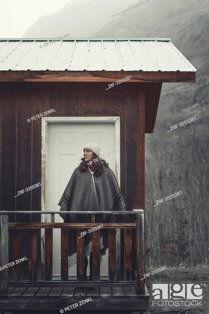 Stock Photo: An attractive Woman with stands in front of her cabin and lets her eyes wander across the cold surroundings. Yukon Territory, Canada.