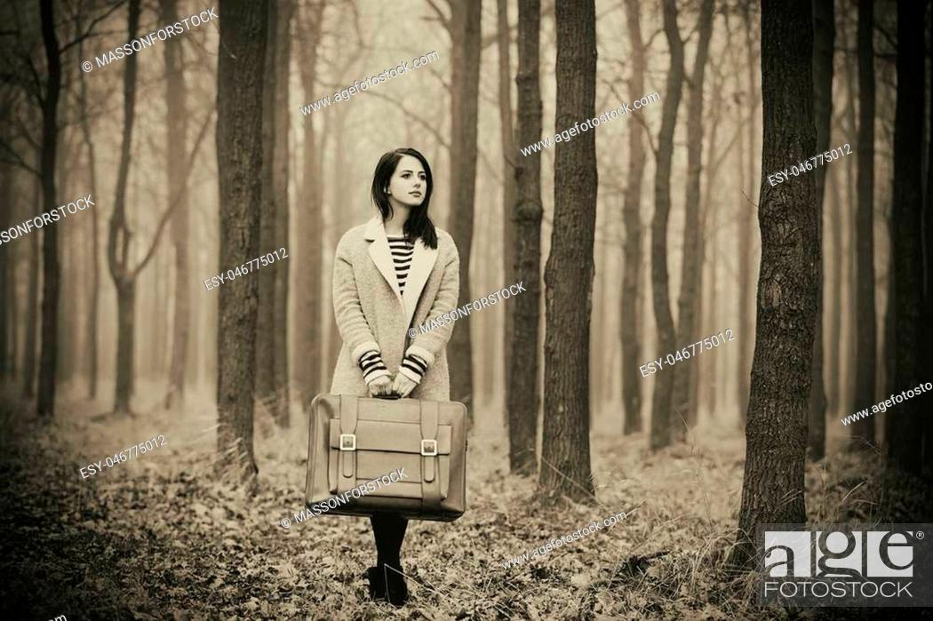 Stock Photo: portrait of a young woman with a suitcase standing in the middle of the forest.