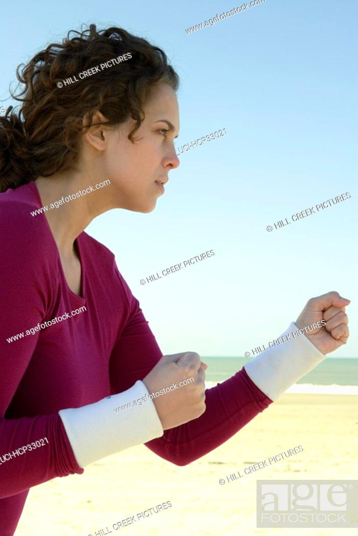 Stock Photo: Woman practicing self-defense at beach.