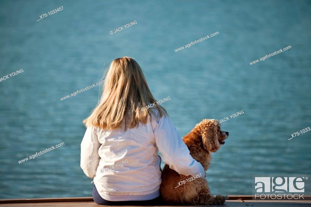 Stock Photo: A young woman and her dog at the lake.