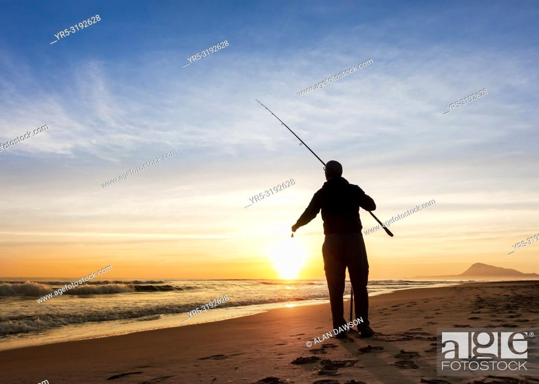 Imagen: Man fishing from beach near Oliva at sunrise on the Costa del Azahar near Denia, Valencia province, Spain, Europe.