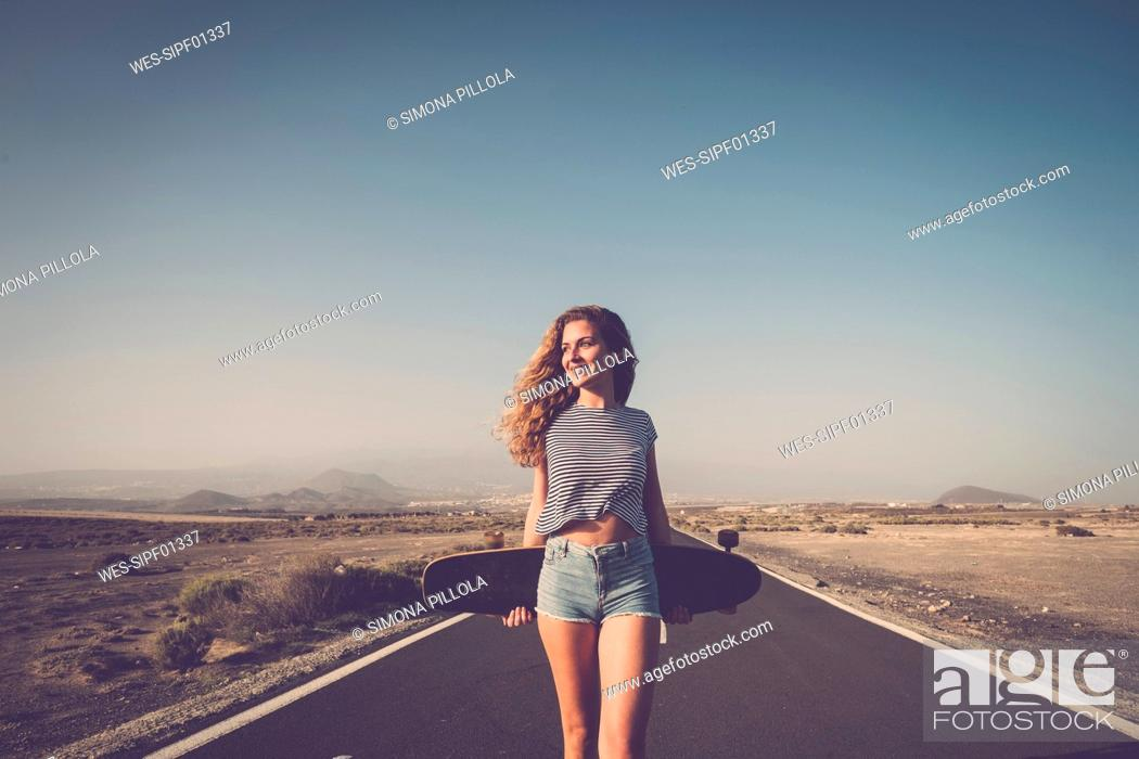 Stock Photo: Spain, Tenerife, smiling woman with longboard standing on empty country road.