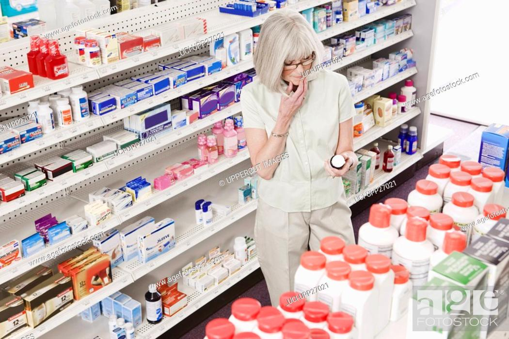 Stock Photo: Woman reading label on bottle in drug store.