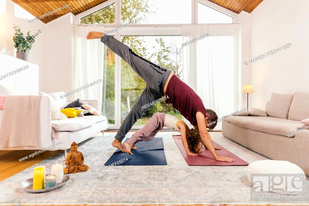 Stock Photo: Father and daughter doing yoga together at home.