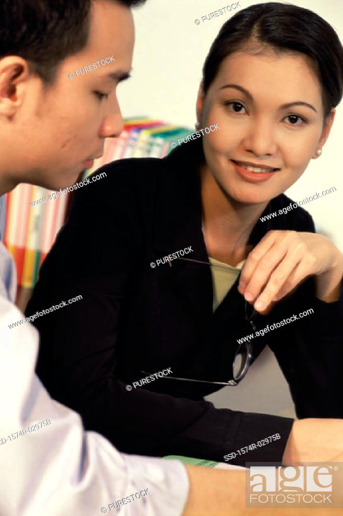 Stock Photo: Portrait of a businesswoman sitting with a businessman.