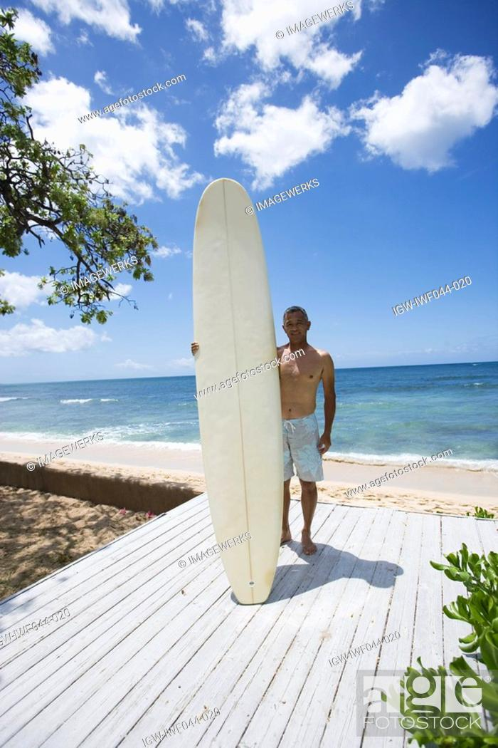 Stock Photo: Mature man standing with surfboard.