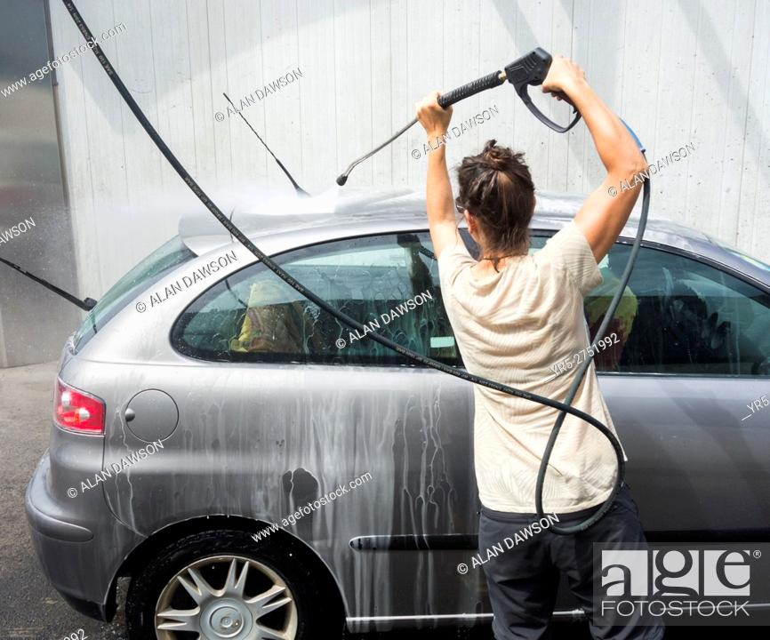 Spanish Woman Washing Car With Pressure Washer In Petrol Station In