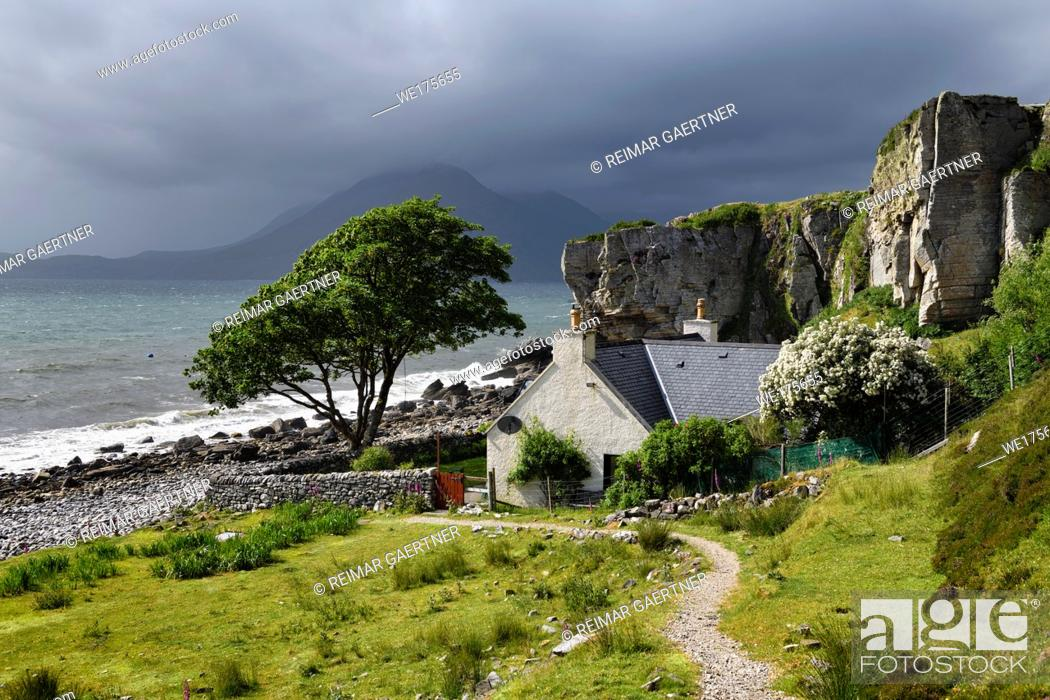 Stock Photo: House under cliff at Elgol beach with Red Cuillin Mountains under clouds at Loch Scavaig Scottish Highlands Isle of Skye Scotland UK.