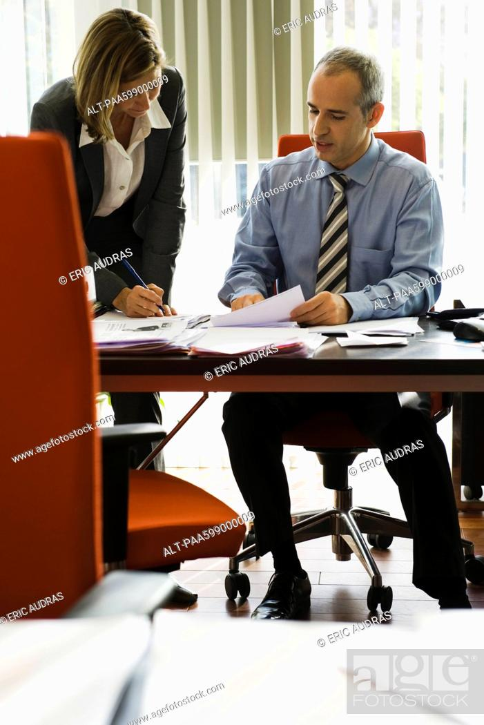 Stock Photo: Businessman talking to female colleague as she making notes.